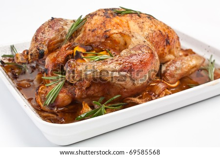 whole roasted stuffed chicken in a dish on white background - stock photo