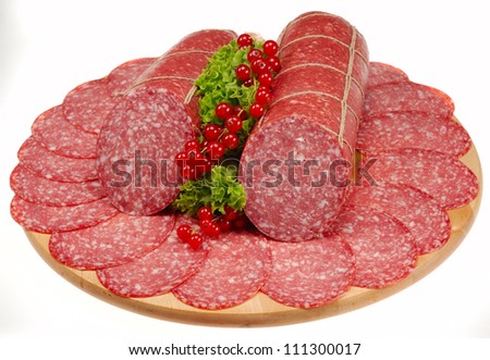 Whole salami surrounded by slices on board. Isolated on white. - stock photo