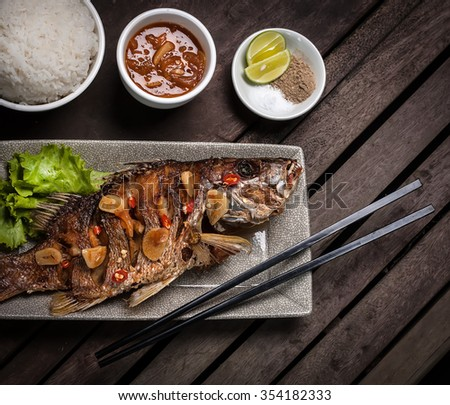 Whole snapper fish fried served with rice, sweet spicy red sauce and seasoning - stock photo