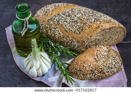 Whole wheat bread and rye, sprinkled with sunflower seeds, poppy seeds, sesame seeds, next to a bottle of olive oil, rosemary and garlic - stock photo