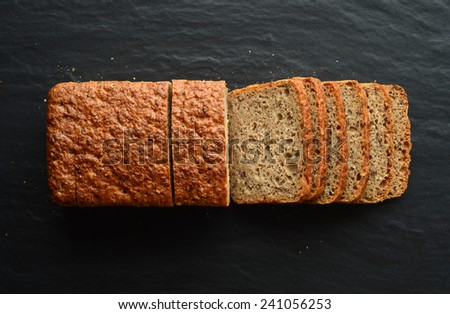 Whole wheat bread on a black stone plate - stock photo