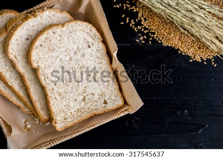 Whole Wheat Bread on Black Wooden Background - stock photo