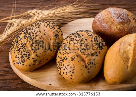 Whole wheat bread with sesame seed on wood. - stock photo