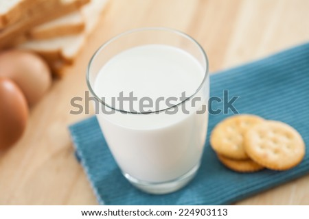 Whole wheat flour bread crackers egg  and milk glass on wooden table background - stock photo