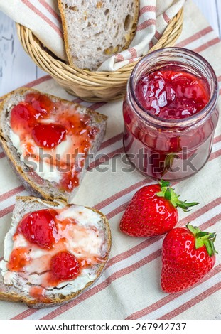 Whole wheat nut bread with cream cheese and strawberry jam closeup - stock photo