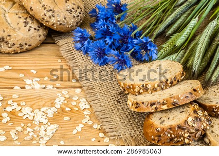 Whole wheat rye bread rolls with ears of cereal and cornflowers located on wood background. Rustic arrangement - stock photo