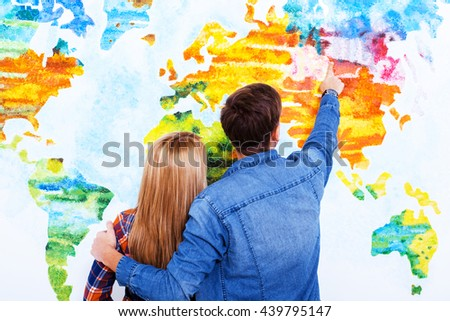 Whole world for us. Two students cuddling and pointing on the map of the world - stock photo