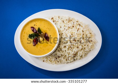 Whole Yellow Lentil with Rice, dal tadka and jeera rice, Indian Dish, cooked rice and cooked Arhar or Toor dal (Pigeon Pea), served in a white plate, isolated view on orange background, top view - stock photo
