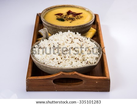 Whole Yellow Lentil with Rice, dal tadka and jeera rice, Indian Dish, cooked rice and cooked Arhar or Toor dal (Pigeon Pea), served in ceramic bowl in a tray, isolated, front view on white background  - stock photo