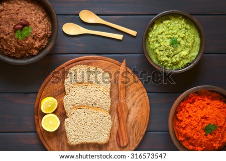Wholegrain bread slices on wooden plate with three bowls of homemade vegetable spreads (red kidney bean, zucchini and parsley, carrot and red bell pepper), photographed overhead with natural light - stock photo