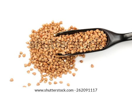 Wholegrain buckwheat in in black wooden spoon, isolated - stock photo