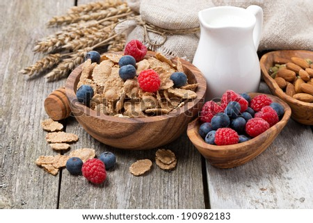 wholegrain flakes with fresh berries, nuts and milk on wooden table, horizontal - stock photo