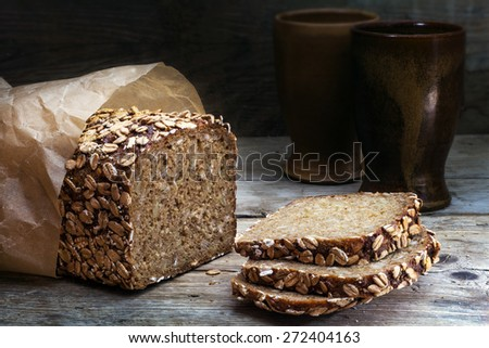 wholegrain rye bread with seeds on a weathered wooden board, rustic earthenware in the dark background - stock photo