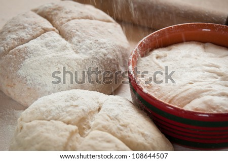 Wholemeal and plain flour dough with sourdough and rolling pin - stock photo
