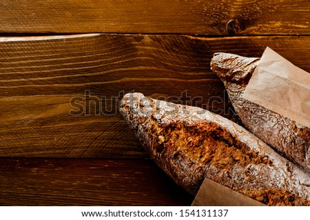 Wholemeal bread on a wooden table - stock photo