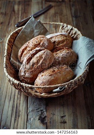 Wholemeal bread rolls in a basket  - stock photo