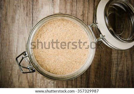 Wholemeal flour in a glass jar, top view - stock photo