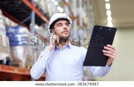 wholesale, logistic, business, export and people concept - businessman with clipboard calling on smartphone at warehouse - stock photo