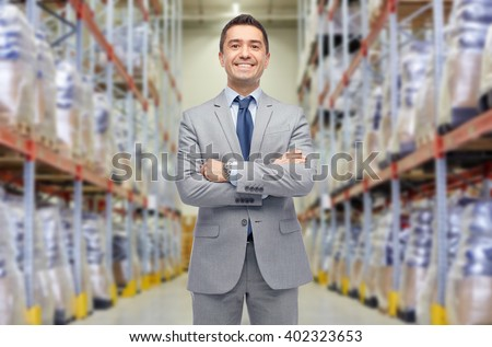 wholesale, logistic, business, export and people concept - happy man in suit and tie at warehouse over warehouse background - stock photo