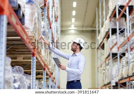 wholesale, logistic, business, export and people concept - man or manager in hardhat with tablet pc computer checking goods at warehouse - stock photo