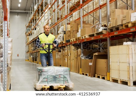 wholesale, logistic, loading, shipment and people concept - man carrying loader with goods at warehouse - stock photo