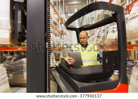 wholesale, logistic, loading, shipment and people concept - man or loader with tablet pc computer and forklift or loader loading boxes at warehouse - stock photo
