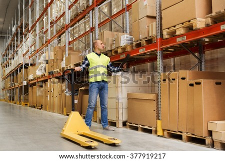 wholesale, logistic, loading, shipment and people concept - man with empty loader and clipboard at warehouse - stock photo