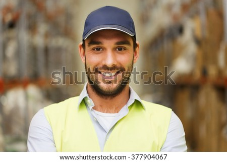 wholesale, logistic, people and export concept - happy man in cap and reflective safety vest at warehouse - stock photo