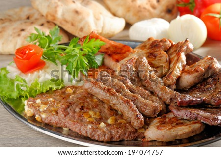 Wholesome platter of mixed meats including grilled steak. Balkan food - stock photo