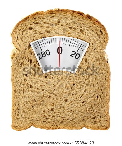 Wholesome slice of bread as weighing scale isolated on white - stock photo