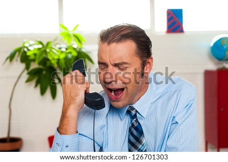 Why are sales so low today? Businessman yelling on phone in his office. - stock photo