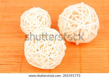 wicker bamboo balls on bamboo mat - stock photo