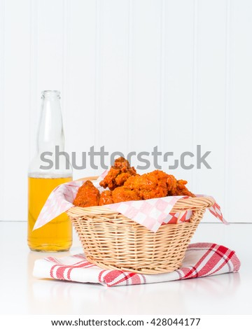 Wicker basket filled with buffalo style chicken wings. - stock photo