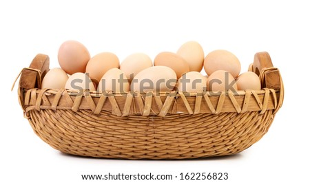 Wicker basket fool with eggs. Isolated on a white background. - stock photo