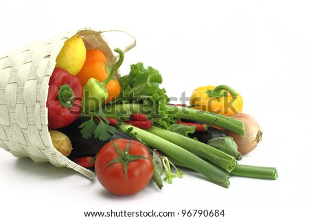 Wicker basket full of fresh vegetables - stock photo