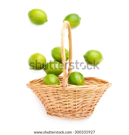 Wicker basket full of multiple ripe green limes, composition isolated over the white background - stock photo