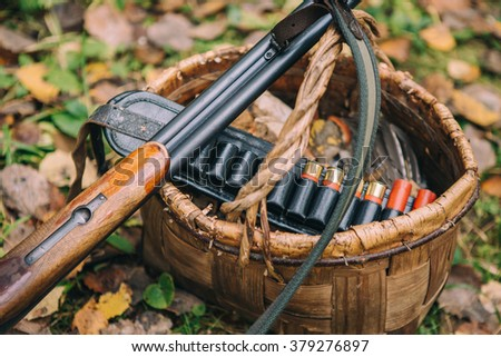 wicker basket, mushrooms, hunter rifle cartridges - stock photo