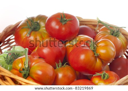 Wicker basket of a mixed collection  of freshly picked heirloom  organic tomatoes isolated on white. - stock photo