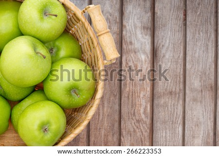Wicker basket of crisp fresh green apples displayed on a wooden picnic table or at a farmers market for fresh produce direct from the farm, overhead view with copy space - stock photo