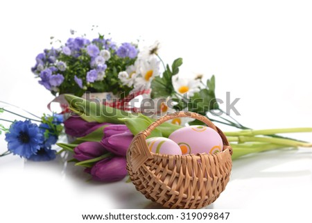 wicker basket of easter eggs with flowers - stock photo