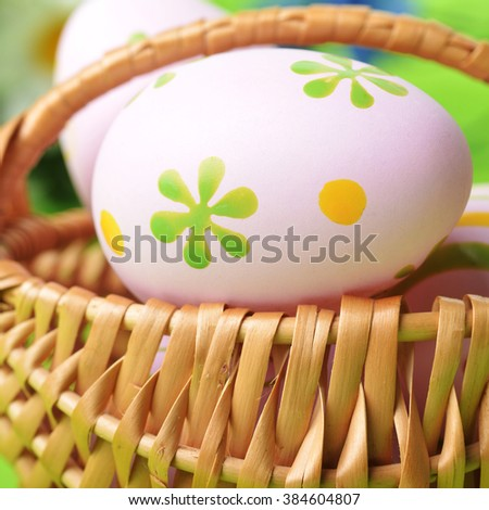 wicker basket of easter eggs with wildflowers on green background - stock photo