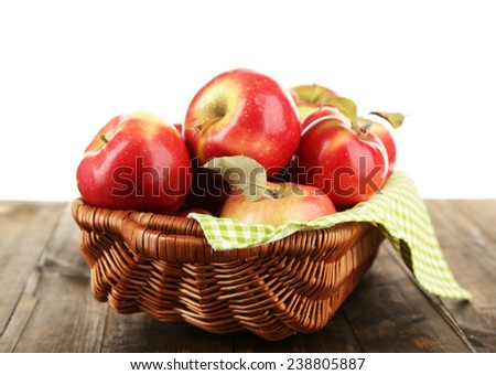 Wicker basket of red apples with napkin on wooden table, isolated on white background - stock photo