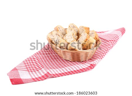 Wicker basket with bread slices on tablecloth. Isolated on a white background. - stock photo