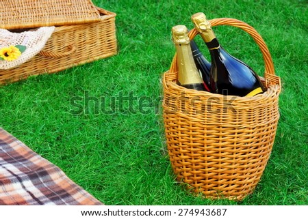 Wicker Basket With Champagne Wine,  Hamper And Blanket On Spring Emerald Color Lawn,Summer Picnic Scene Concept - stock photo