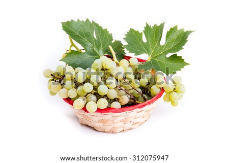 Wicker basket with clusters of white grapes isolated on white background - stock photo