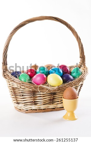 Wicker basket with colored eggs on a white background. Happy Easter. - stock photo