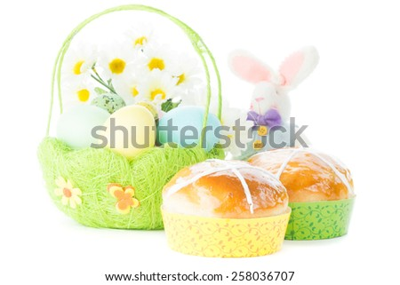 Wicker Basket with Easter eggs, spring flowers, hot cross buns and cute rabbit - stock photo