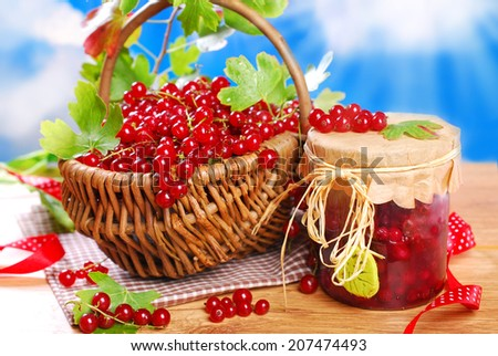 wicker basket with fresh red currant and jar of homemade preserve on wooden garden table - stock photo
