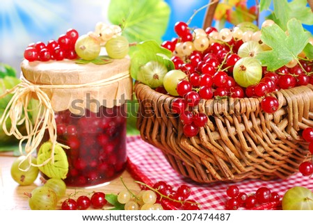 wicker basket with fresh red,white currant,gooseberry  and jar of homemade preserve on wooden garden table - stock photo