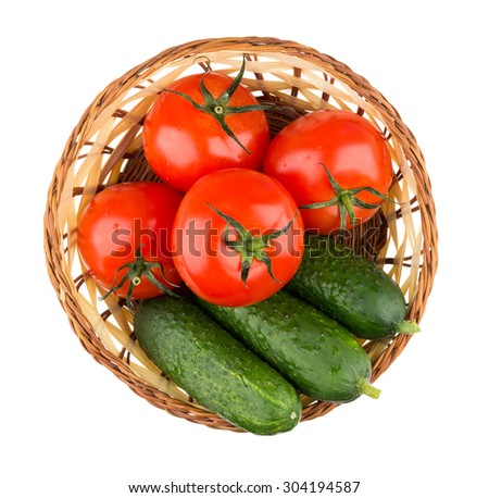 Wicker basket with fresh tomatoes and cucumbers isolated on white background, top view - stock photo